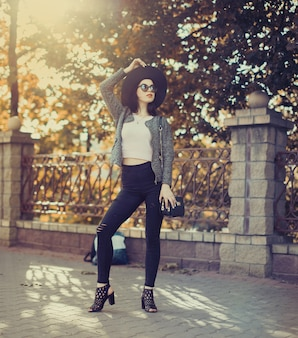 Morena com lábios vermelhos no chapéu e óculos de sol posando na cidade