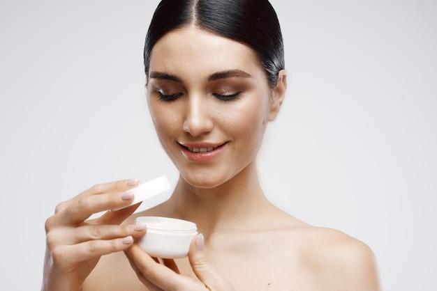 Morena com ombros nus em frasco de creme dermatologia