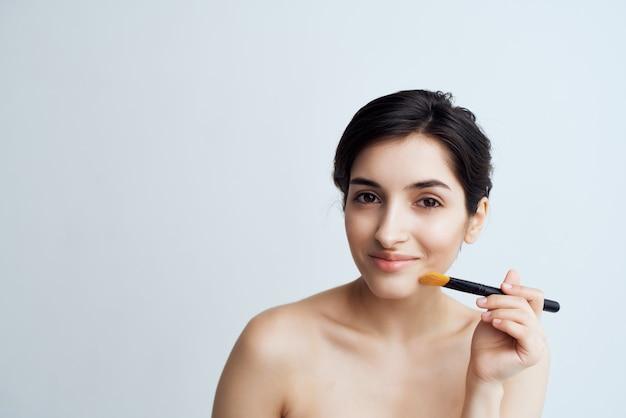Morena com ombros nus para maquiagem facial