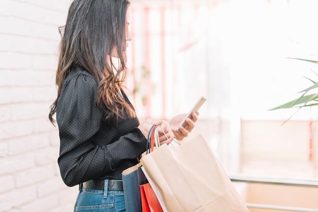 Morena com sacos e smartphone na luz