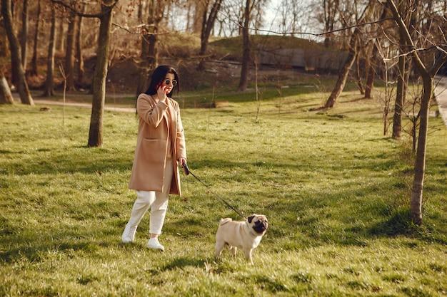 Morena com um casaco marrom caminha com pug