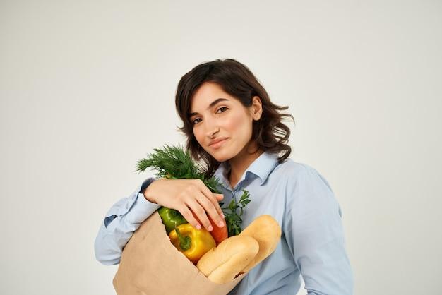 Morena com um pacote de alimentos saudáveis do supermercado vegetais de alimentos