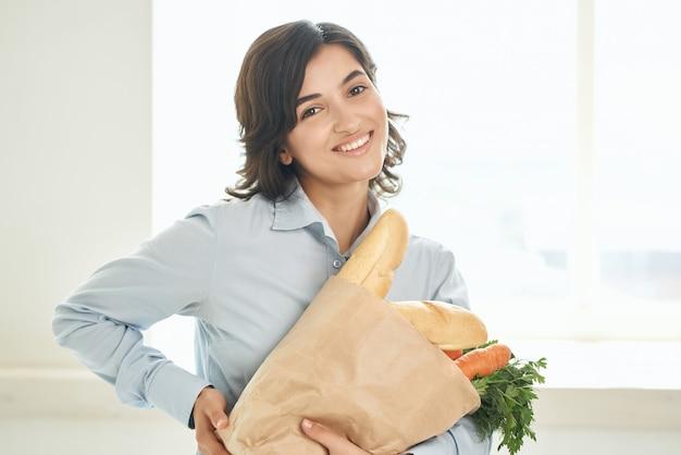 Morena com um pacote de mantimentos dona de casa estilo de vida supermercado