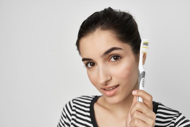 Morena com uma camiseta listrada segurando uma escova de dentes para limpar os dentes e higiene bucal