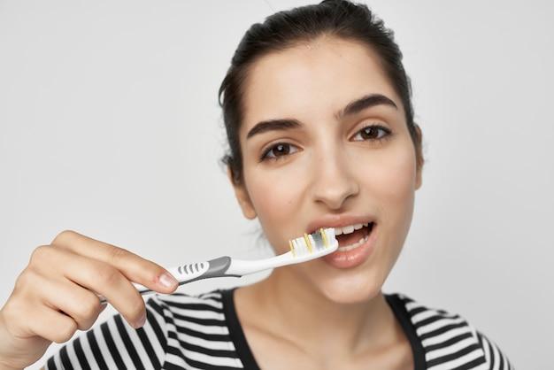 Morena com uma escova de dentes de camiseta listrada na mão isolado fundo