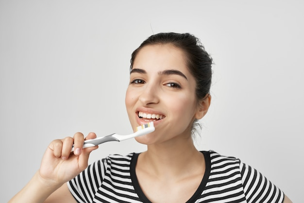 Morena com uma escova de dentes listrada na mão luz de fundo