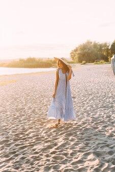 Morena com uma roupa de verão elegante e chapéu de palha sob os raios de sol na caminhada pela natureza
