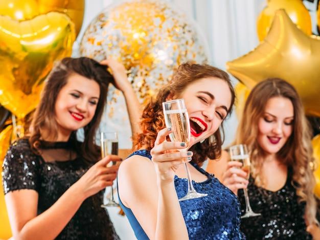 Morena comemorando com as madrinhas de casamento no próximo dia especial. garotas se divertindo, bebendo champanhe.