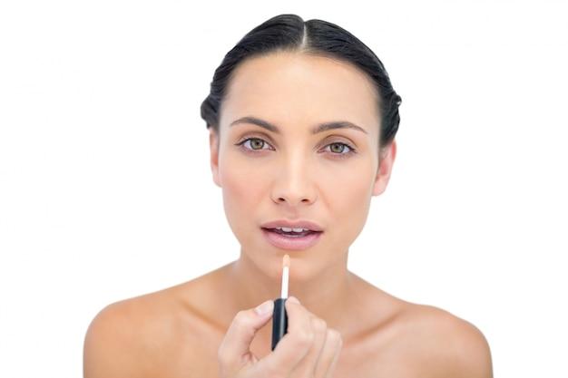 Morena concentrada jovem aplicando brilho labial