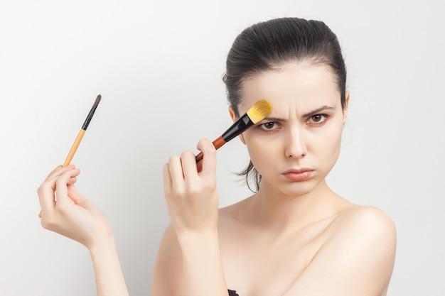 Morena creme de escovação na visão recortada de cuidados com a pele do rosto.
