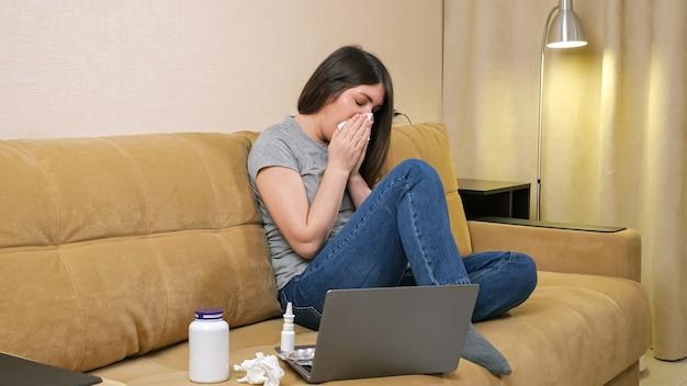 Morena de cabelos compridos espirra olhando para a tela do laptop