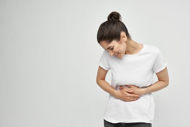 Morena de camiseta branca segurando a barriga menstruação problemas de saúde insatisfação