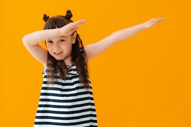 Morena de criança menina faz motion dab trend na parede amarela isolada. blogueiros infantis modernos