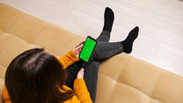 Morena de jeans sentada no sofá com tela verde do smartphone