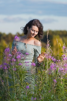 Morena de mulher jovem alegre retrato em um vestido azul com um buquê de flores roxas, caminhando no campo.
