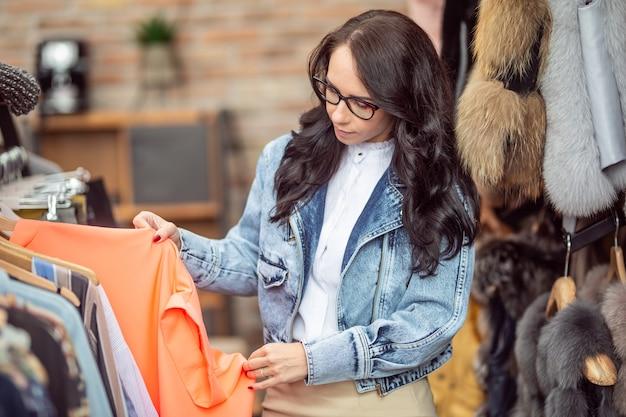 Morena de óculos olha para as roupas no rack da loja de moda.