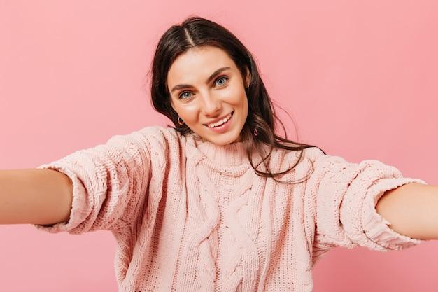 Morena de olhos azuis olha para a câmera e sorri. rapariga com camisola de malha faz selfie em fundo rosa.