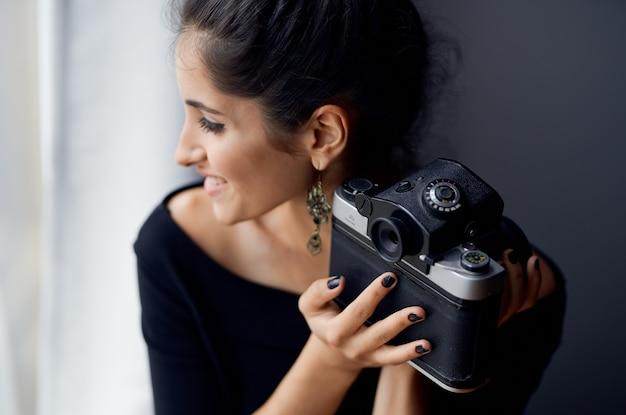 Morena de vestido preto perto da janela posando de estúdio de estilo de vida