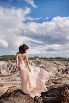 Morena de vestido rosa fica em um penhasco, o vento irrita um vestido