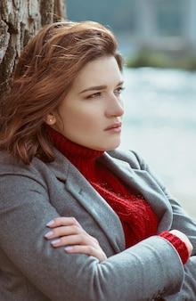 Morena deprimida mulher triste à beira do rio na cidade no fundo da ponte