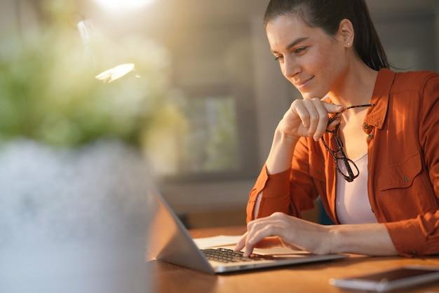 Morena deslumbrante trabalhando no computador em casa