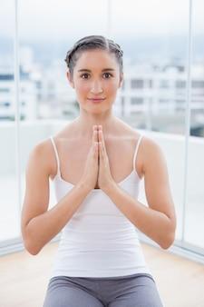 Morena desportiva de sorriso que senta-se na postura da ioga
