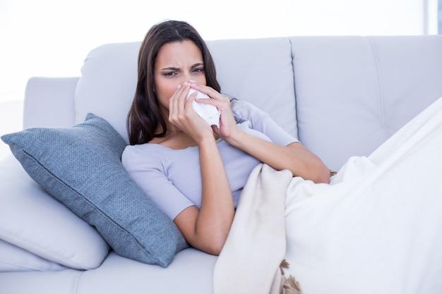 Morena doente deitada no sofá e soprando o nariz