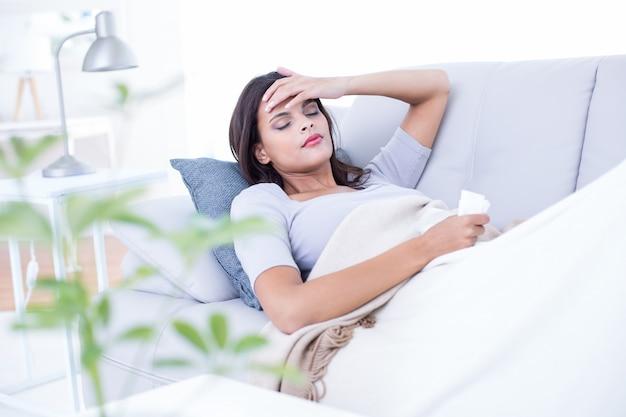 Morena doente deitada no sofá