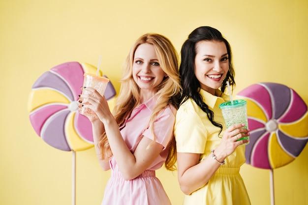 Morena e loira com vestidos brilhantes em uma parede amarela. vestido rosa e amarelo. pirulito grande.