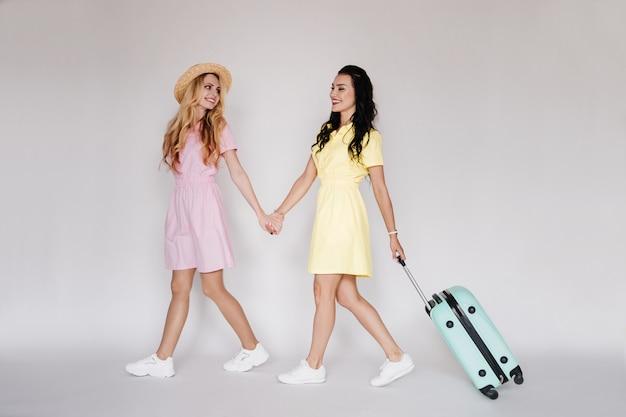 Morena e loira com vestidos brilhantes em uma parede branca com um chapéu de palha. vestido rosa e amarelo. viajando com uma mala de menta.