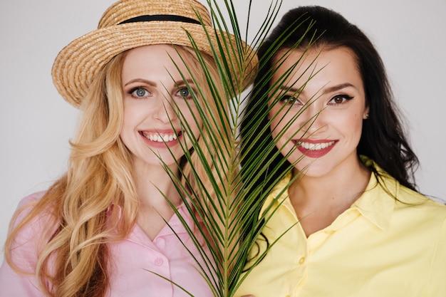 Morena e loira com vestidos brilhantes em uma parede branca com um chapéu de palha. vestido rosa e amarelo.