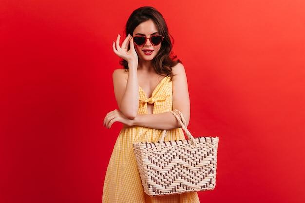 Morena elegante com vestido de verão amarelo coloca óculos em forma de coração. menina com bolsa de praia, posando na parede vermelha.