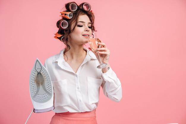 Morena elegante, dona de casa com um copo de álcool e um ferro na parede rosa