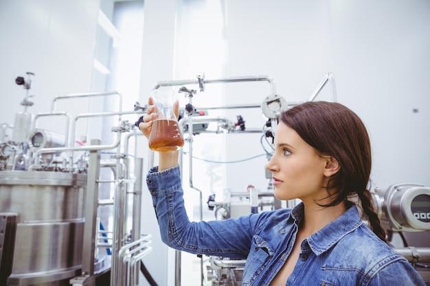 Morena elegante na jaqueta jeans, olhando para o copo de cerveja