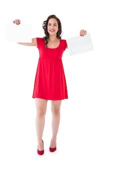 Morena elegante no vestido vermelho segurando páginas