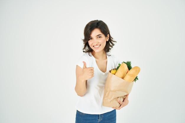 Morena em tshirt branca gesto positivo com pacote de mãos com produtos de qualidade de mercearia