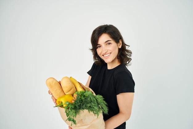 Morena em um pacote de t-shirt preta com supermercado de legumes de mercearia. foto de alta qualidade