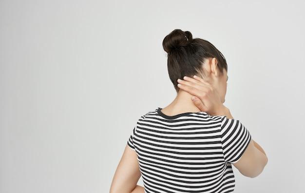 Morena em uma camiseta listrada problemas de saúde dor de cabeça enxaqueca. foto de alta qualidade