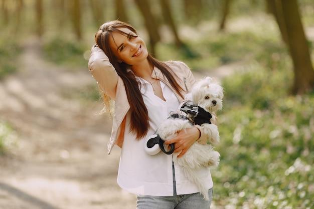 Morena em uma floresta caminha com cachorro fofo