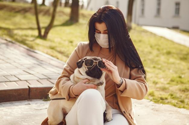 Morena em uma máscara caminha com pug