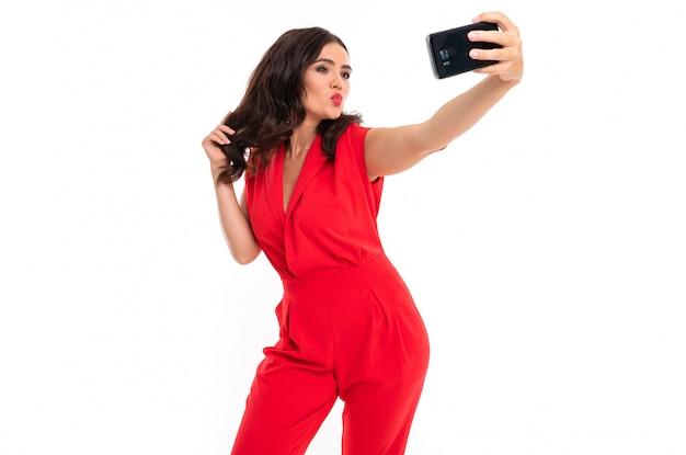 Morena em uma superfície branca com uma roupa vermelha tira uma selfie