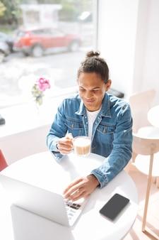 Morena encantada mantendo um sorriso no rosto enquanto olha para a tela de seu laptop