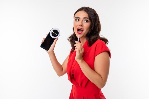 Morena encantadora caucasiana jovem vídeo blogger grava vídeo no telefone com um dispositivo de flash em um fundo branco