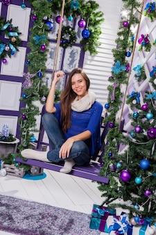 Morena encantadora de jeans e um suéter azul senta-se em um balanço no natal