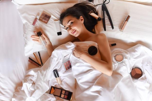 Morena encantadora deitada na cama com produtos de beleza