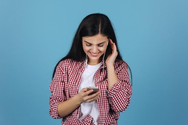 Morena encantadora escuta a música em seus fones de ouvido, segurando um smartphone