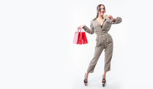 Morena encantadora posando com pacotes vermelhos e um cartão do banco