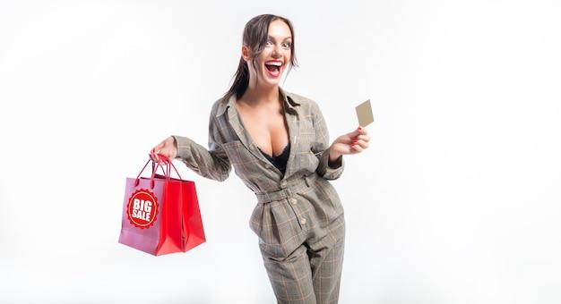 Morena encantadora posando no estúdio com pacotes vermelhos e um cartão do banco. conceito de presente. compras antes das férias. fundo branco. mídia mista