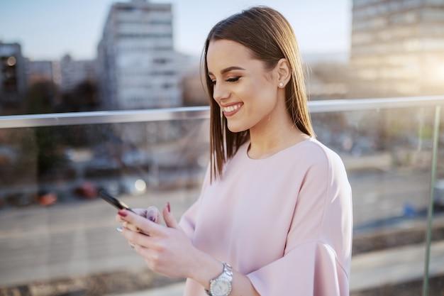 Morena encantadora vestido elegante sorrindo e usando telefone inteligente no telhado