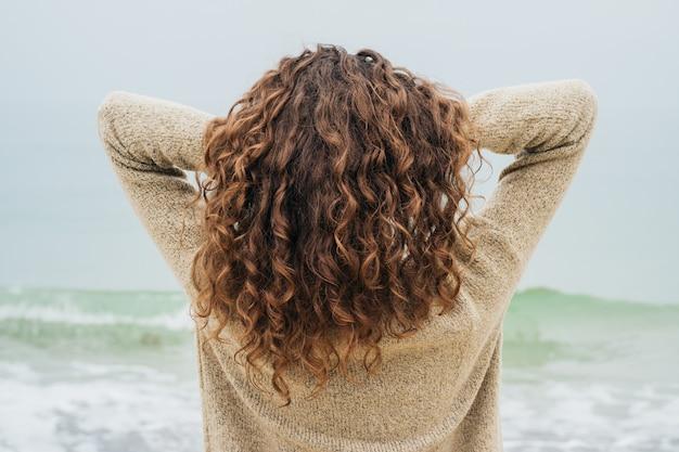 Morena encaracolada em um suéter na costa enfrenta o mar e alisa o cabelo